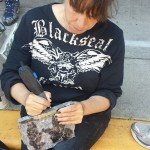 Here you can view the artist etching her signature on the bottom of a stone carving of two bear toddlers.